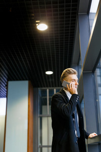 Thoughtful blond-haired white collar worker using smartphone while standing in office lobby and enjoying view from panoramic window, profile view