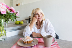 Thoughtful senior woman sitting at the kitchen table with breakfast and looking away