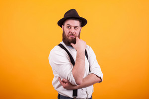 Thoughtfull bearded man with hat keeping his arms crossed over yellow background. Stylish hat. Handsome man.