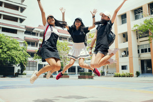 three asian teenager jumping mid air with happiness emotion against school building background