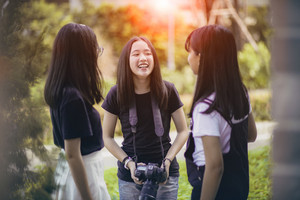 three asian teenager  with dslr camera in hand pose as fashion model