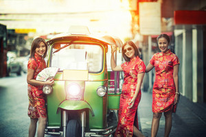 three asian woman wearing chinese traditon clothes standing beside tuktuk in yaowaratch road chinatown bangkok thailand