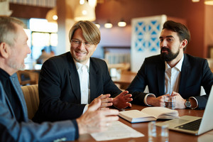 Three businessmen sharing ideas about financial tendencies