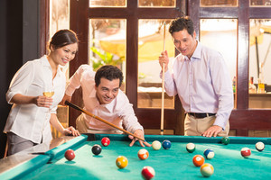 Three colleagues playing billiards after work