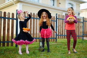 Three ecstatic girls in Halloween costumes