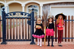 Three girls standing by gate with Halloween treats