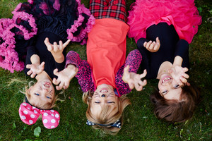 Three girls with frightening expression lying on grass
