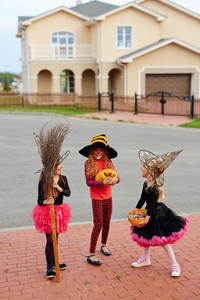 Three halloween characters with broom, treat candies and pumpkin having talk outdoors