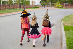 Three Halloween witches having trick-or-treat walk