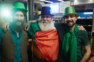 Three happy buddies in Irish costumes in pub