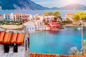 Tile chimney in front of Assos village. Beautiful view to vivid colorful houses near blue turquoise colored transparent bay lagoon. Kefalonia, Greece