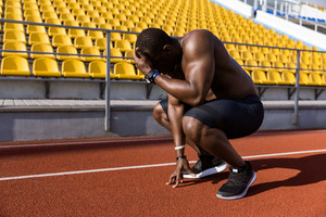 Tired african male athlete finished running and resting while sitting on a racetrack