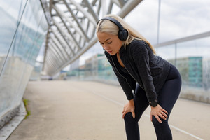 Tired Female Runner Resting With Hands On Knees After Workout