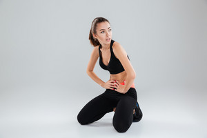Tired fitness woman sitting on the floor with hands on hip over gray background