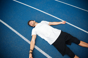 Tired male athlete resting after running while lying on a racetrack at the stadium