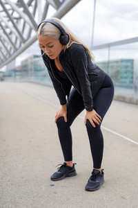 Tired Woman Resting With Hands On Knees After Running Workout