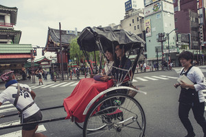 TOKYO JAPAN - SEP 12,2015 : tourist laughing with happiness emotion sitting on rickshaw in front of Sensoji Asakusa Kannon Temple most popular traveling destination in tokyo