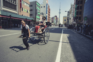 TOKYO JAPAN - SEP 12,2015 : unidentified tourist sitting on rickshaw moving on street in heart of tokyo township with tokyo tower on background