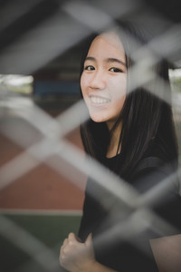 toothy smiling face of asian teenager relaxing emotion