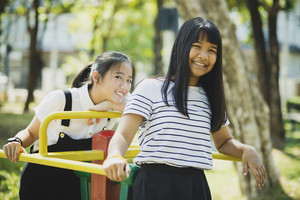 toothy smiling face of asian teenager relaxing in children playground