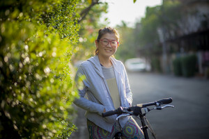 toothy smiling face of asian woman standing with bicycle on village street