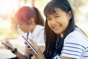 toothy smiling face of cheerful asian teenager holding smart phone in hand