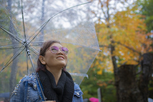 toothy smiling face of woman tourist with rain umbrella standing in autumn color leaves in hokkaido japan ,hokkaido is most popular autumn season traveling destination in japan