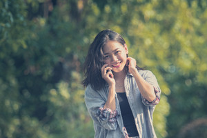 toothy smiling face of younger asian woman talking on mobile phone in green park