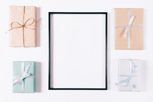 Top view of a box with gifts and blank frame on a white background