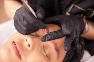 Top view of caucasian woman removing an eyebrow tattoo in a beauty salon. Skin care. Body care. Hygiene procedure.