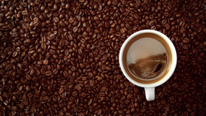 top view of cup of black coffe put it on coffe beans background. White cup of black coffee