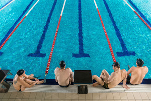 Top view of four male swimmers sitting on the edge of a swimming pool
