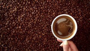 top view of hand with cup of black coffe put it on coffe beans background. White cup of black coffee