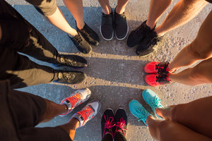 Top view of runners standing in a huddle with their feet together