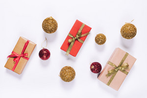 Top view of several gift boxes in wrapping paper with ribbon and Christmas balls on a white background