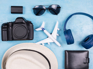 Top view of travel planing for holiday on blue background. Hat. Dalr. Headphones. Sunglasses.