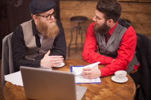 Top view of two bearded man having a meeting a coffeee shop. Stylish men. Handsome men. Long beard. Caucasian men.