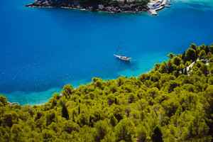 Top view of white lonely yacht in beautiful turquoise colored bay lagoon water surrounded by pine and cypress trees along the coastline. Assos village, Kefalonia island, Greece
