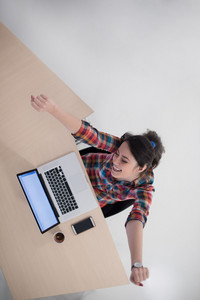top view of young business woman working on laptop computer in modern bright startup office interior
