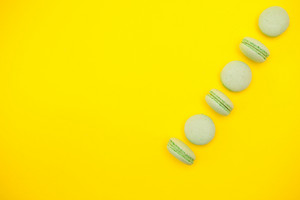 Top view row of green french macaroons over yellow background. Sugar dessert