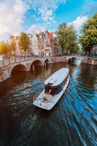 Tour boat at famous Dutch canal on a sunny day, traditional Dutch bridges, medieval houses. Amsterdam Holland