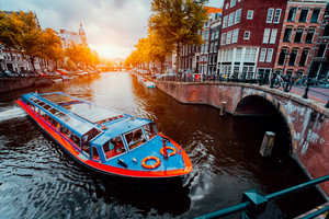 Tour boat at famous Dutch canal on sunset evening. Traditional Dutch bridges and medieval houses. Amsterdam Holland