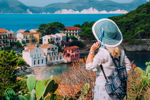 Tourist blond women with sun hat in cute colorful small Assos village. Kefalonia, Greece