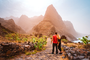 Tourist couple in Aranhas valley hiking from Cruzina to Ponta do Sol. Huge mountains of coastline and old local stone house in the background. Santo Antao Island, Cape Verde