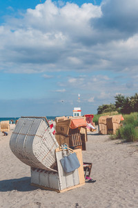 Tourist resting relax in striped roofed chairs on sandy beach in Travemunde. , Lubeck, Germany
