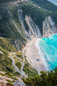 Tourist tent on famous Myrtos Beach. Big foam waves rolling towards the bay. Kefalonia, Greece