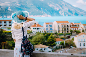 Tourist woman admiring view of colorful tranquil village Assos on morning. Young stylish female model wearing blue sunhat and white clothes enjoying summer travel vacation in Kefalonia, Greece