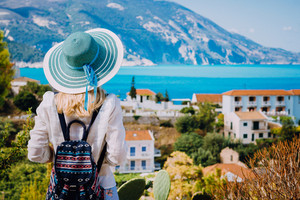 Tourist woman with blue sunhat and travel backpack admire view of colorful tranquil village Assos on sunny day. Visiting Kefalonia during summer time on Greece travel vacation