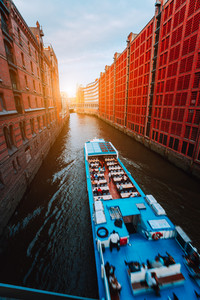 Touristic cruise boat in narrow canal of famous Speicherstadt warehouse district with red brick buildings in Hamburg, Germany