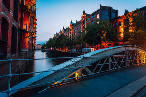 Touristic spot of old bridge and red brick illuminated buildings, canal and square in golden sunset light. Speicherstadt Hamburg. Warehause District at dawn